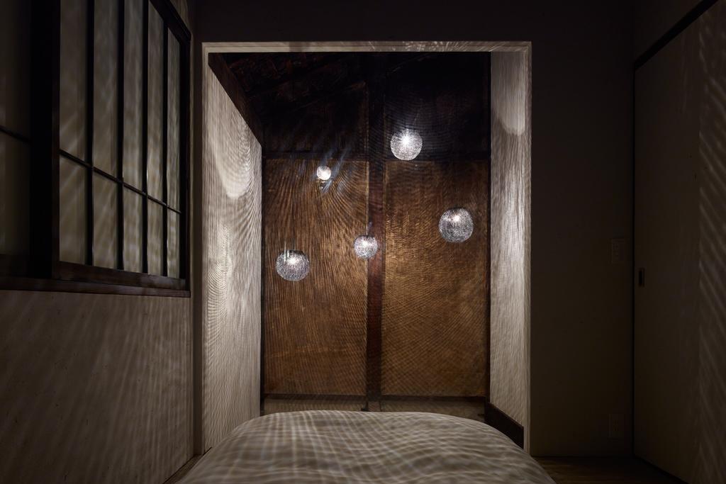 吹き抜けの照明器具は、和束町でかぶせ茶を生産する際の遮光シートを使用。2階の和室はガラス張りになっており、幻想的な光に包まれる。