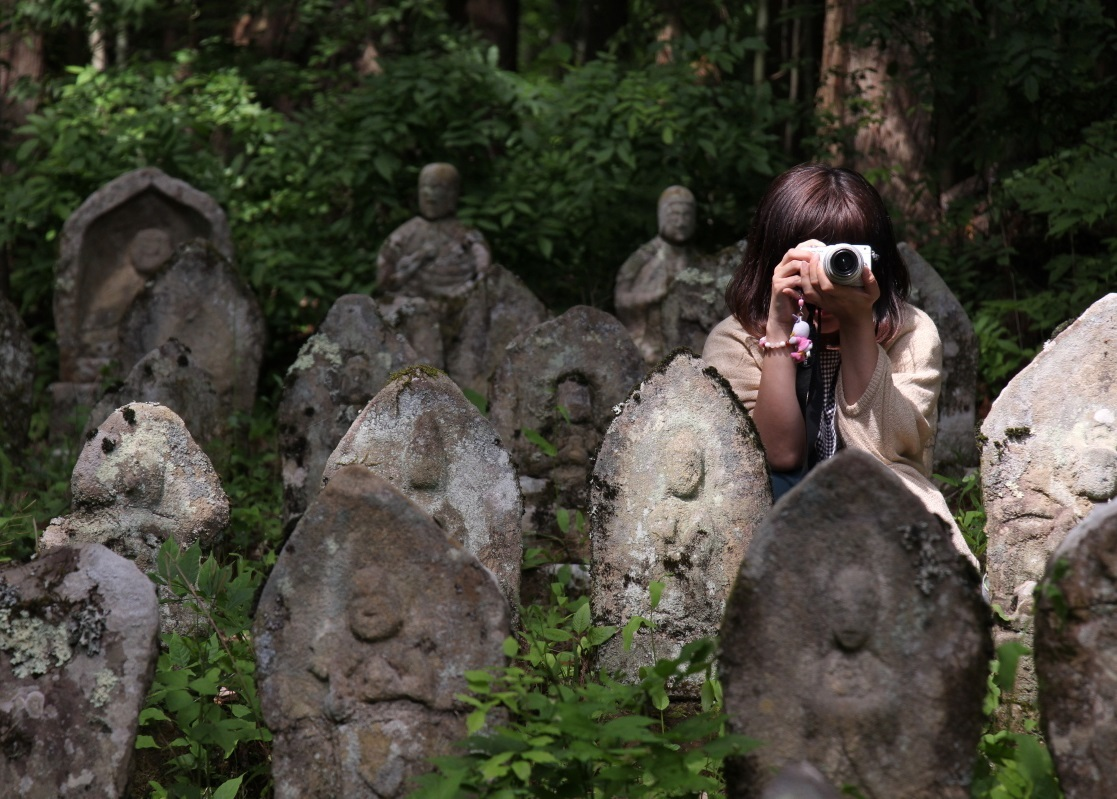 長野県池田町での双体道祖神ツアー下見のために池田町を訪れた際の1枚。山本さんの周りに立っているのは百体観音と呼ばれる石仏群